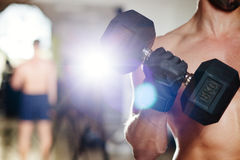 Athletic male with dumbbells workout. In gym Royalty Free Stock Photos