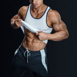 Athletic male model posing, pulling up tank top Stock Images