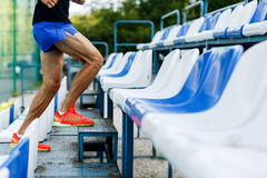 Athletic male with muscular legs up stairs of stadium outdoors. Portrait of athletic male with muscular legs up stairs of stadium outdoors on summertime Stock Image