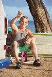 Athletic Male Surfer Relaxing. Athletic single male surfer gesturing at ocean beach Stock Photography
