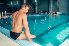 Athletic male swimmer sits on the curb, back view Royalty Free Stock Photos