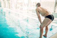 Athletic male swimmer sits on the curb, back view Stock Photo