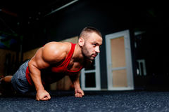 Athletic male training on a gym background. Handsome sports man doing push-ups. Indoor exercising concept. Copy space. Close-up of a gorgeous sports man doing Stock Photo
