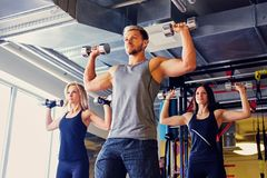 Athletic male and two slim female fitness models doing shoulder exercises with dumbbells. Handsome blond, athletic male and two slim female fitness models doing Royalty Free Stock Photos