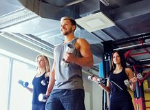 Athletic male and two slim female fitness models doing shoulder exercises with dumbbells. Handsome blond, athletic male and two slim female fitness models doing Royalty Free Stock Images