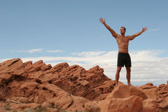 Athletic man. On red stones royalty free stock photography