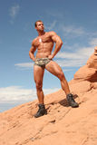 Athletic man. On red stones stock photos