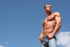 Athletic man. In blue jeans stock images
