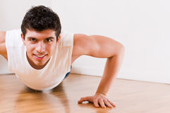 Athletic man. Young athletic man doing push-ups while smiling and looking at camera stock photos