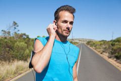 Athletic man adjusting his earphones on a run Stock Images