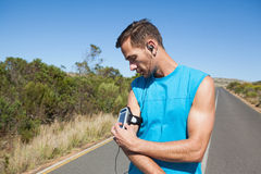 Athletic man adjusting his music player on a run Stock Images