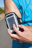 Athletic man adjusting his music player on a run Royalty Free Stock Image