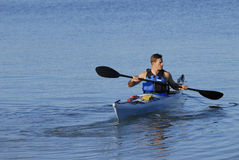Athletic man backs into bay in kayak. An athletic man is backing off the shore into calm blue waters of Mission Bay, San Diego, California. Copy space on top and Stock Images