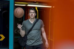 Sporty Man With a Basketball Walking out of a Subway Train. Athletic man with a basketball in hand walking out of a subway train in Frankfurt. Medium shot royalty free stock images