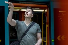 Sporty Man With a Basketball Walking out of a Subway Train. Athletic man with a basketball in hand walking out of a subway train in Frankfurt. Medium shot royalty free stock image