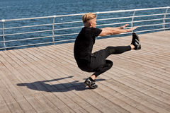 Athletic man bobbing on pier. Side view of fit adult man bobbing on one leg on a pier. Horizontal outdoors shot Stock Photo