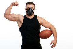 Athletic man boxer with rugby ball. A young athletic man sportsman in a sports T-shirt, training black mask show biceps and holds in his hand a rugby ball on stock photo