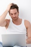 Athletic man browsing internet on laptop Stock Photos
