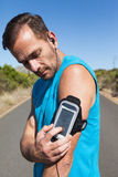 Athletic man changing the music on a run Stock Photos