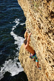 Athletic man climbing on a rock Stock Photography