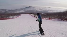 Athletic man confidently rolls down the mountain on a snowboard. He professionally goes from side to side on the empty stock video footage