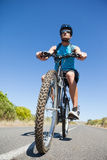 Athletic man cycling on open road Royalty Free Stock Photography
