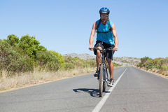 Athletic man cycling on open road Royalty Free Stock Images