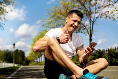 Athletic man with devices in winking and showing thumbs-up. Cheerful male is sitting on road in countryside and using earphones with smartphone. He is showing ok Stock Images