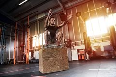 Athletic man does box jump exercises at the gym Stock Images