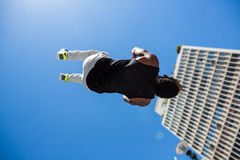 Athletic man doing back flip in the city Stock Photos