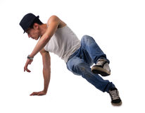 Athletic man doing a break dance routine. Athletic trendy young man in a hat doing a break dance routine twirling and kicking his foot in the air while balancing Royalty Free Stock Photography