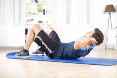 Athletic Man Doing Curl Ups Exercise at Home Stock Photos