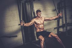 Athletic man doing exercises on training apparatus at the Gym's studio Royalty Free Stock Images
