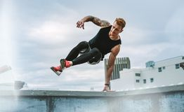 Athletic man doing fitness training on rooftop. Fitness man jumping on to the rooftop from the roof fence taking support of one hand. Man in fitness wear jumping stock photography