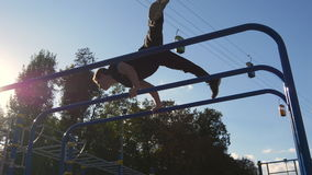 Athletic man doing gymnastics elements on bar in city park. Male sportsman performs strength exercises during workout stock video footage