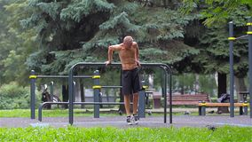 Athletic man doing gymnastics elements on bars in City Park stock video footage