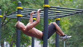 Athletic man doing gymnastics elements in City Park stock video footage