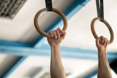 Muscle-up exercise athletic man doing intense workout at gym on gymnastic rings Royalty Free Stock Photo