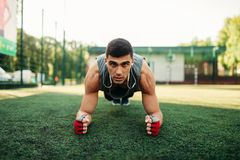 Man doing push-up exercise on a grass outdoor royalty free stock photo