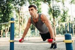 Man doing push-up exercise using horizontal bar stock photos