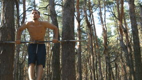 Athletic man doing push ups on horizontal bars at the forest. Strong young muscular guy training in the wood in summer. Athlete exercising outdoor. Workout stock footage