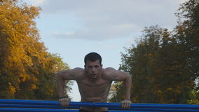 Athletic man doing push ups on parallel bars at sports ground in city park. Strong young muscular guy training outdoor. In summer. Athlete exercising at stock footage