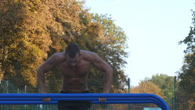 Athletic man doing push ups on parallel bars at sports ground in city park. Strong young muscular guy training outdoor. In summer. Athlete exercising at stock video footage