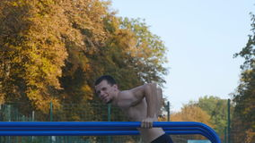 Athletic man doing push ups on parallel bars at sports ground in city park. Strong young muscular guy training outdoor. In summer. Athlete exercising at stock video