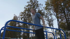 Athletic man doing push ups on parallel bars at sports ground in city park. Strong young muscular guy training outdoor stock video
