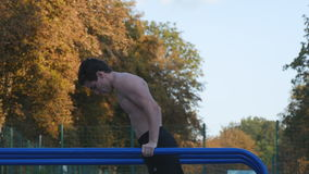 Athletic man doing push ups on parallel bars at sports ground in city park. Strong young muscular guy training outdoor stock video footage