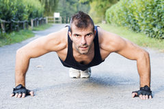 Athletic man doing pushup outdoor. Royalty Free Stock Photography
