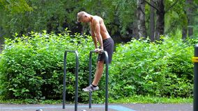 Athletic man doing pushups on bars in City Park. side view. Workout. stock footage