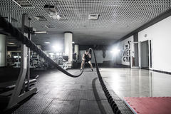 Athletic man doing some cross-training exercises with a rope in gym. Crossfit. Athletic man doing some cross-training exercises with a rope in gym Royalty Free Stock Photography