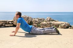 Athletic man doing stretching exercise, preparing for workout on seashore. Handsome fitness athlete doing a stretching routine. Athletic man doing stretching Stock Photo
